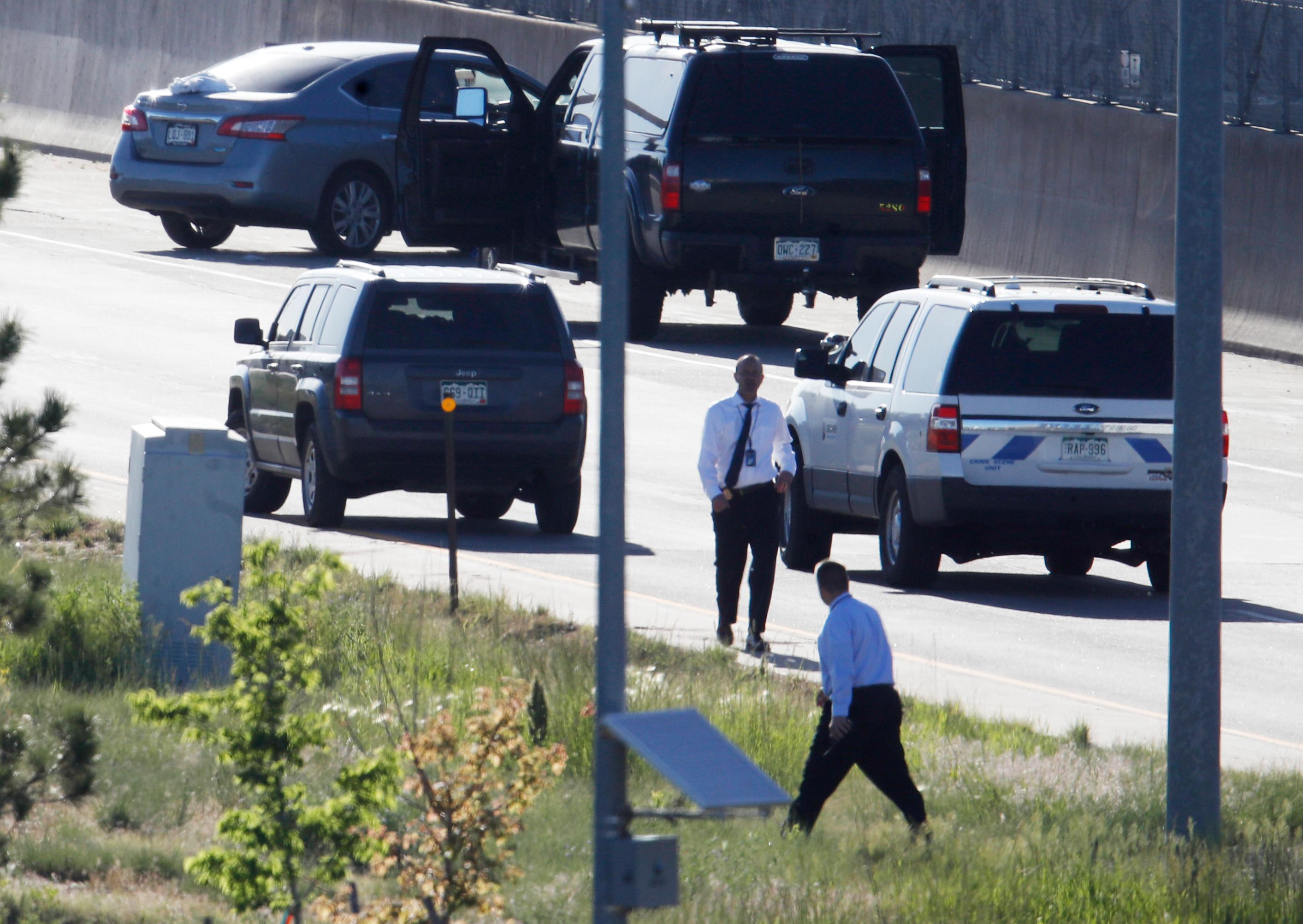 Denver Police Department detectives, foreground, investigate near where a Nissan sedan, top left, being driven by an Uber driver crashed into a retaining wall along Interstate 25 south of downtown Denver early Friday, June 1, 2018. (AP Photo/David Zalubowski)