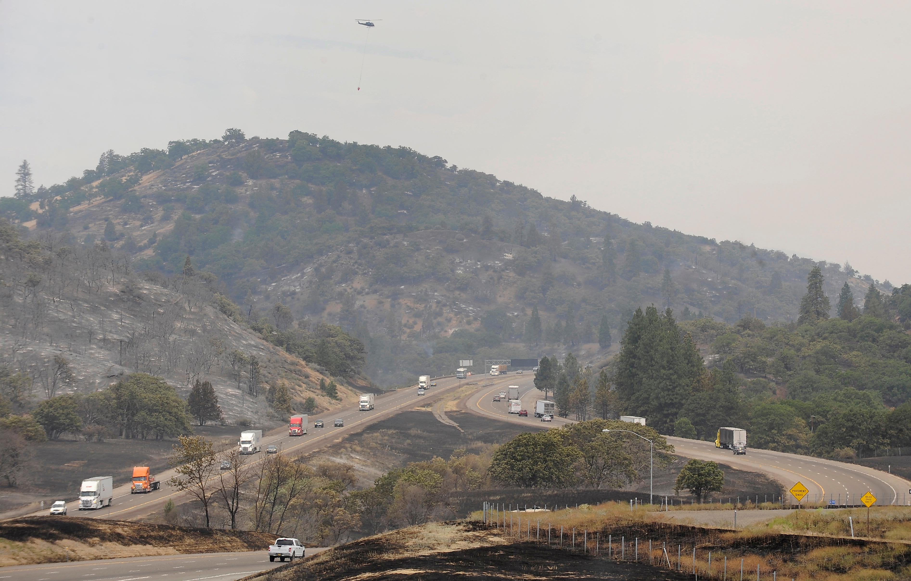 Andy Atkinson / Mail Tribune<br>A helicopter flies over I-5 to fight the fires burning a few miles south of the Oregon-California border Friday afternoon.
