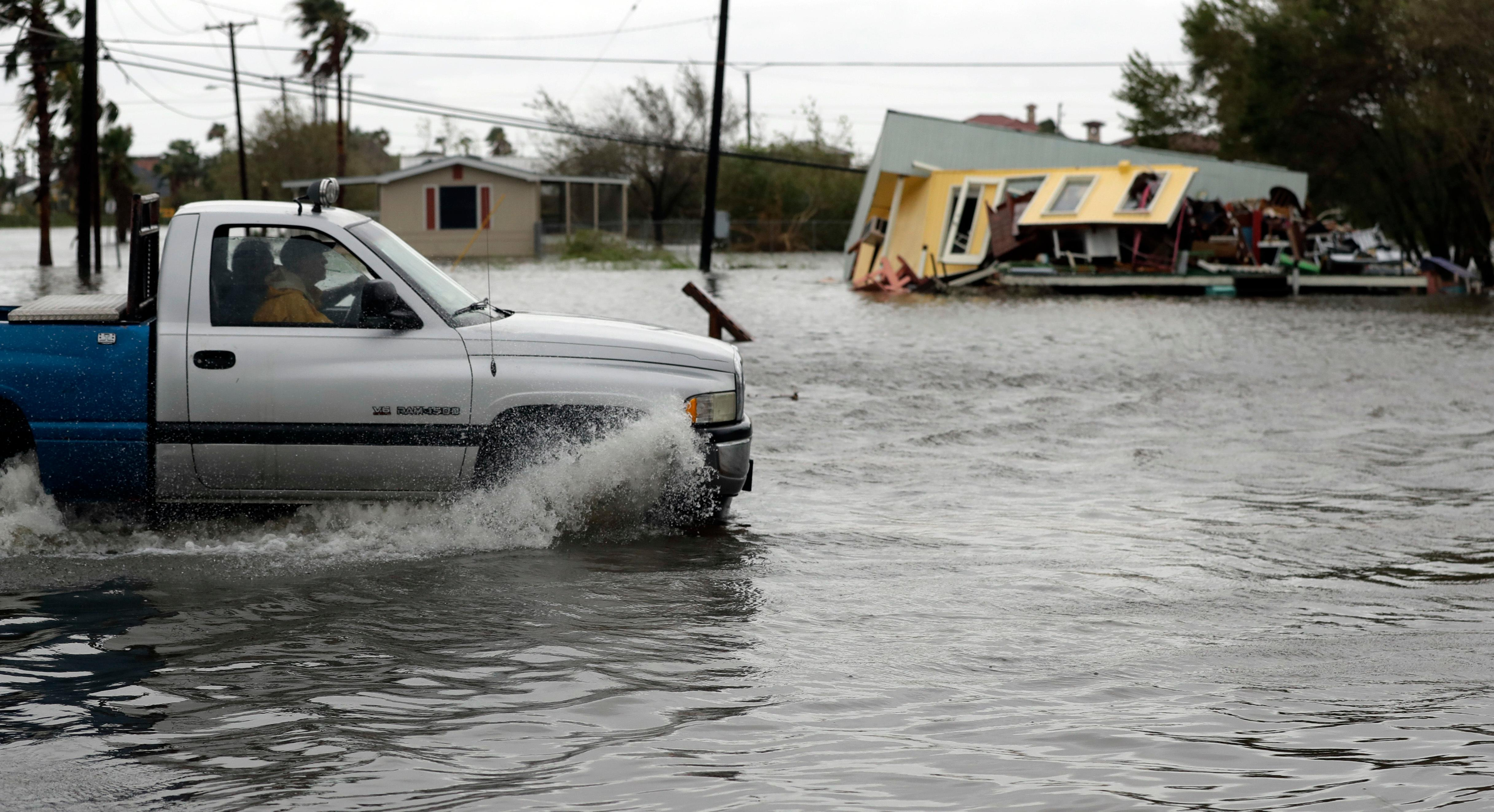 A truck in flood waters passes a home damaged in the wake of Hurricane Harvey, Saturday, Aug. 26, 2017, in Aransas Pass, Texas.  Harvey rolled over the Texas Gulf Coast on Saturday, smashing homes and businesses and lashing the shore with wind and rain so intense that drivers were forced off the road because they could not see in front of them. (AP Photo/Eric Gay)
