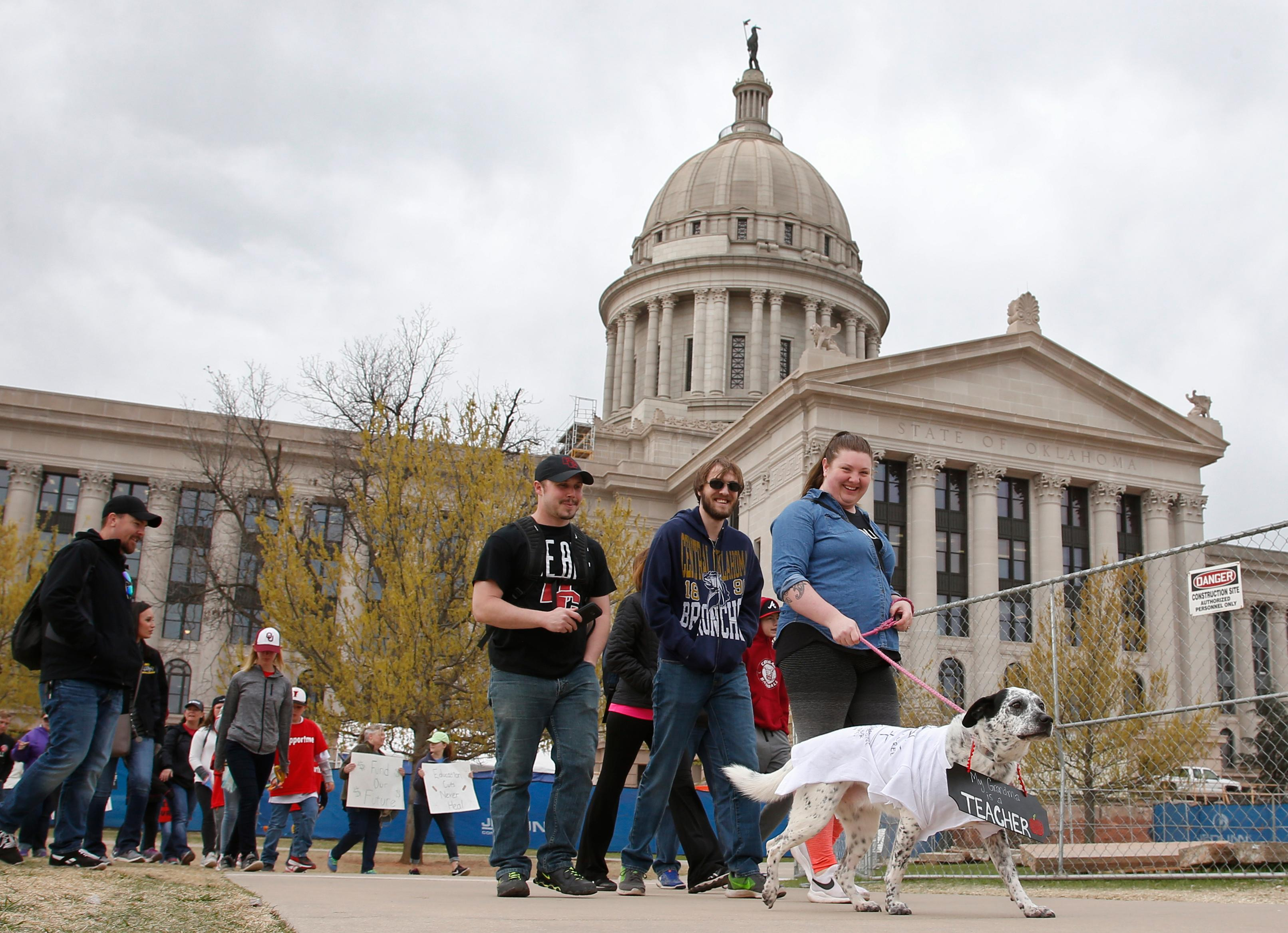 Luna marches with her owner Carlin George, of Oklahoma City, who is at the state Capitol to support her mother, who is a teacher, on the fourth day of protests over school funding, in Oklahoma City, Thursday, April 5, 2018. (AP Photo/Sue Ogrocki)
