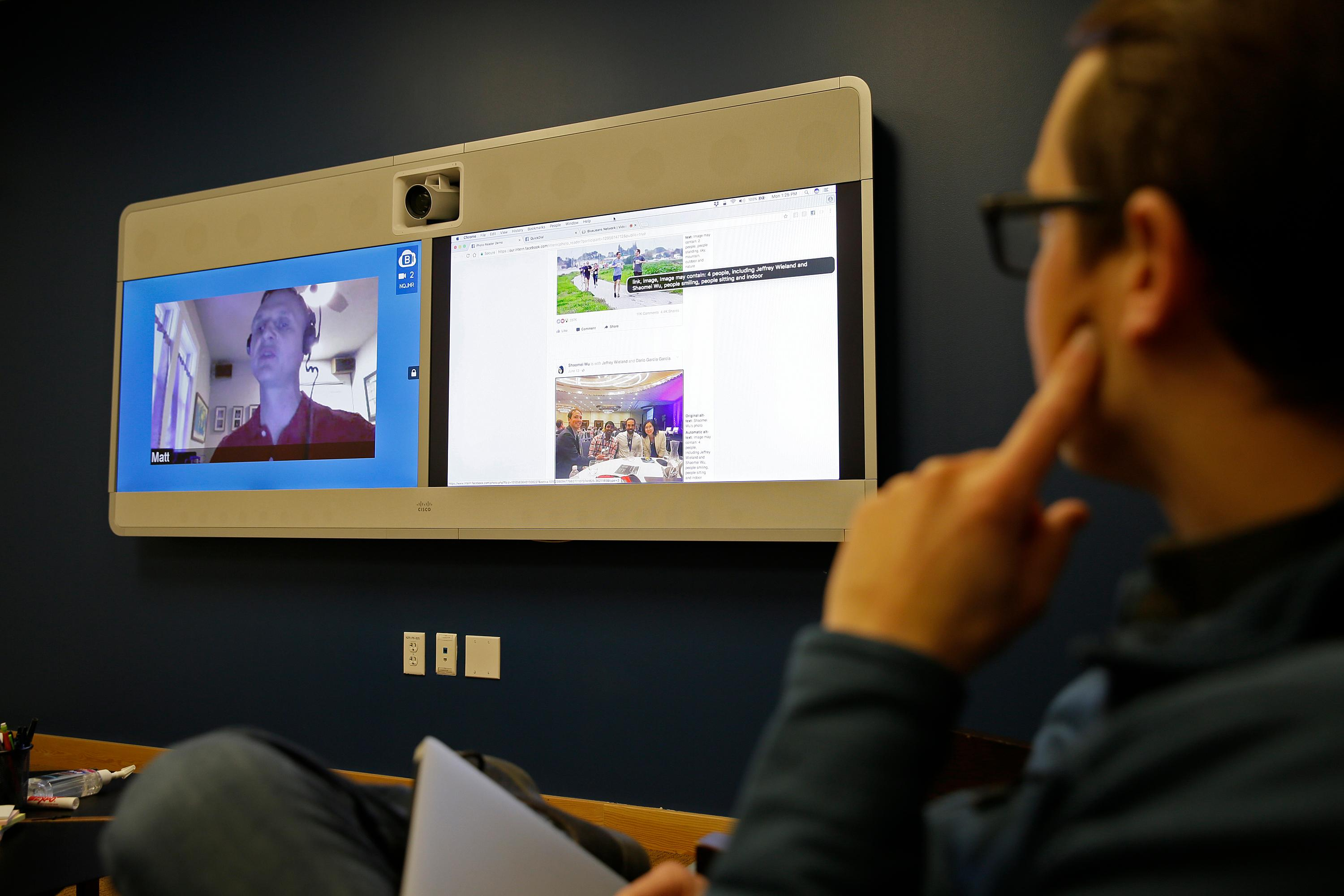 In this photo taken Monday, Dec. 18, 2017, Jeff Wieland,, right, Facebook director of accessibility, watches as engineer Matt King, who is blind, demonstrates facial recognition technology via a teleconference at Facebook headquarters in Menlo Park, Calif. Facebook is unveiling a new AI-powered feature just in time for alcohol-filled holiday parties: you can now see untagged pictures of your face on your friend's news feeds and ask the poster to remove them. (AP Photo/Eric Risberg)