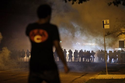 A man watches as police walk through a cloud of smoke during a clash with protesters Wednesday, in Ferguson, Mo.