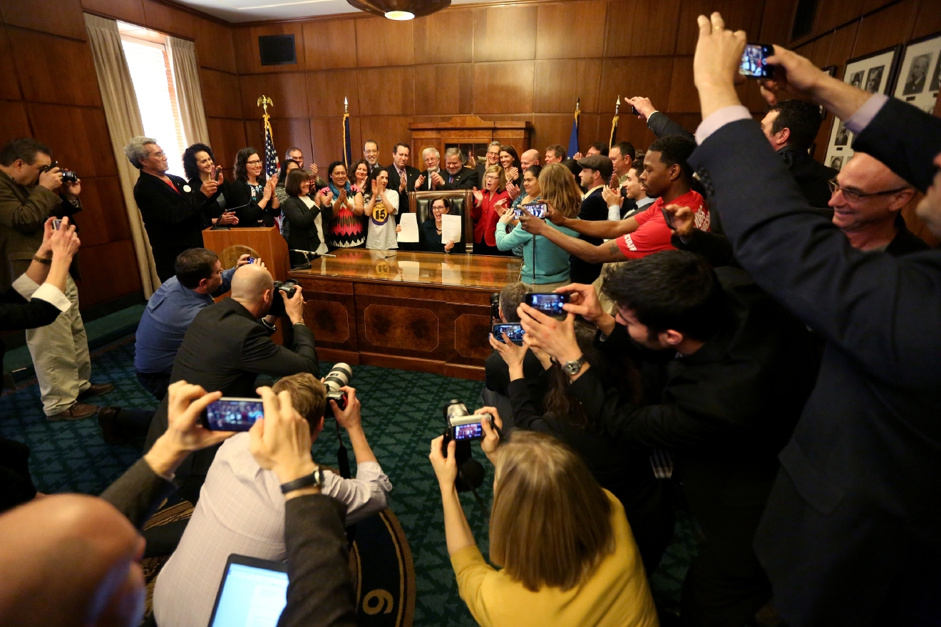 People take photos as Gov. Kate Brown signs Senate Bill 1532, increasing Oregon's minimum wage according to a tiered system, at the State Capitol in Salem on Wednesday, March 2, 2016. PortlandÂ?s minimum will rise to $14.75 by 2022, suburban areas to $13.50 and rural areas to $12.50. The tiered approach is based on economic factors.  (Anna Reed/Statesman-Journal via AP) MANDATORY CREDIT