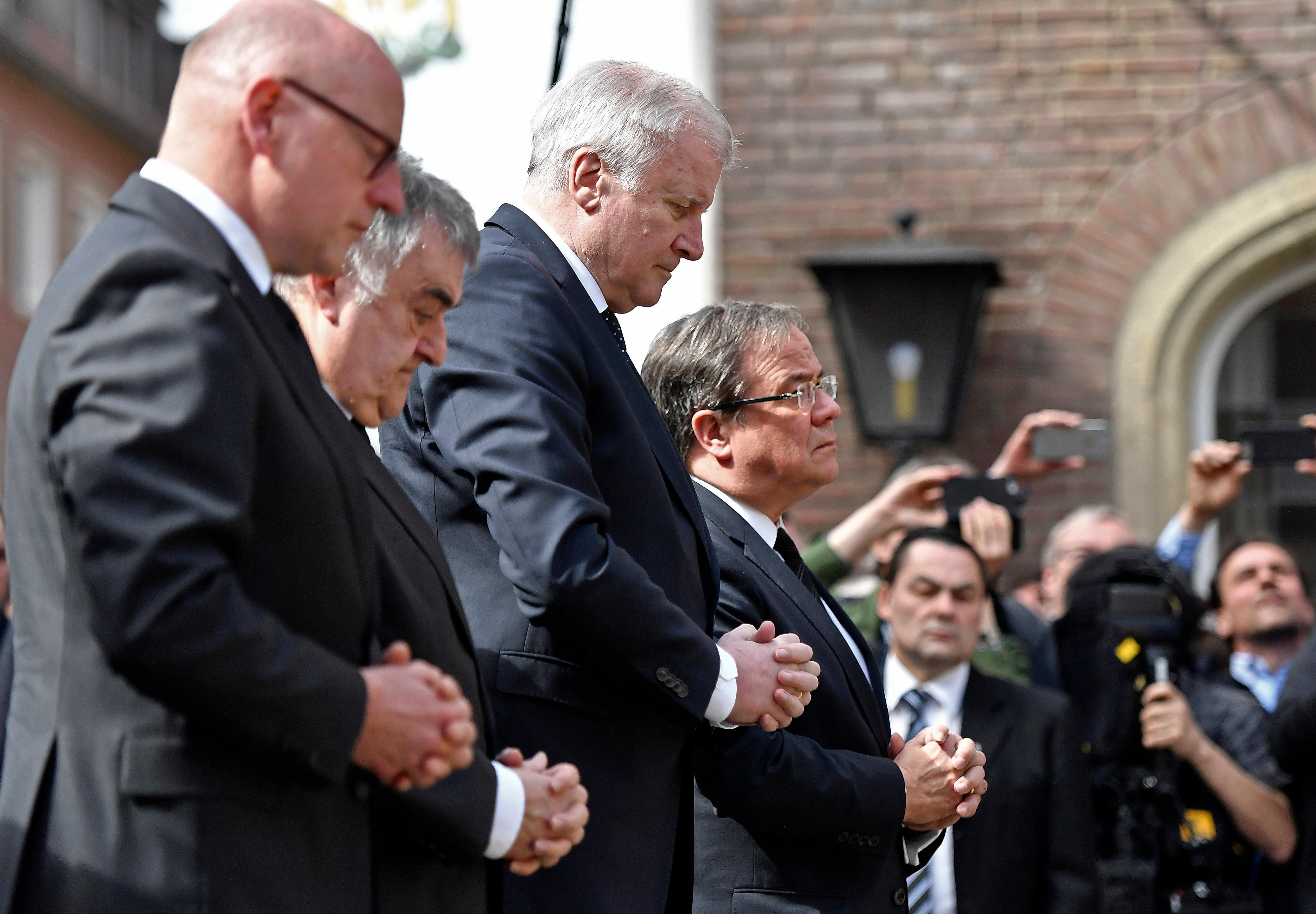 German interior minister Horst Seehofer, center, prays with interior minister of North Rhine-Westphalia Herbert Reul,  second  left, governor Armin Laschet, right,  and the mayor of Muenster Markus Lewe, left, at the place in Muenster, Germany, Sunday, April 8, 2018 where a vehicle crashed into a crowd yesterday. A van crashed into people drinking outside a popular bar Saturday in the German city of Muenster, killing two people and injuring 20 others before the driver of the vehicle shot and killed himself inside it, police said. (AP Photo/Martin Meissner)