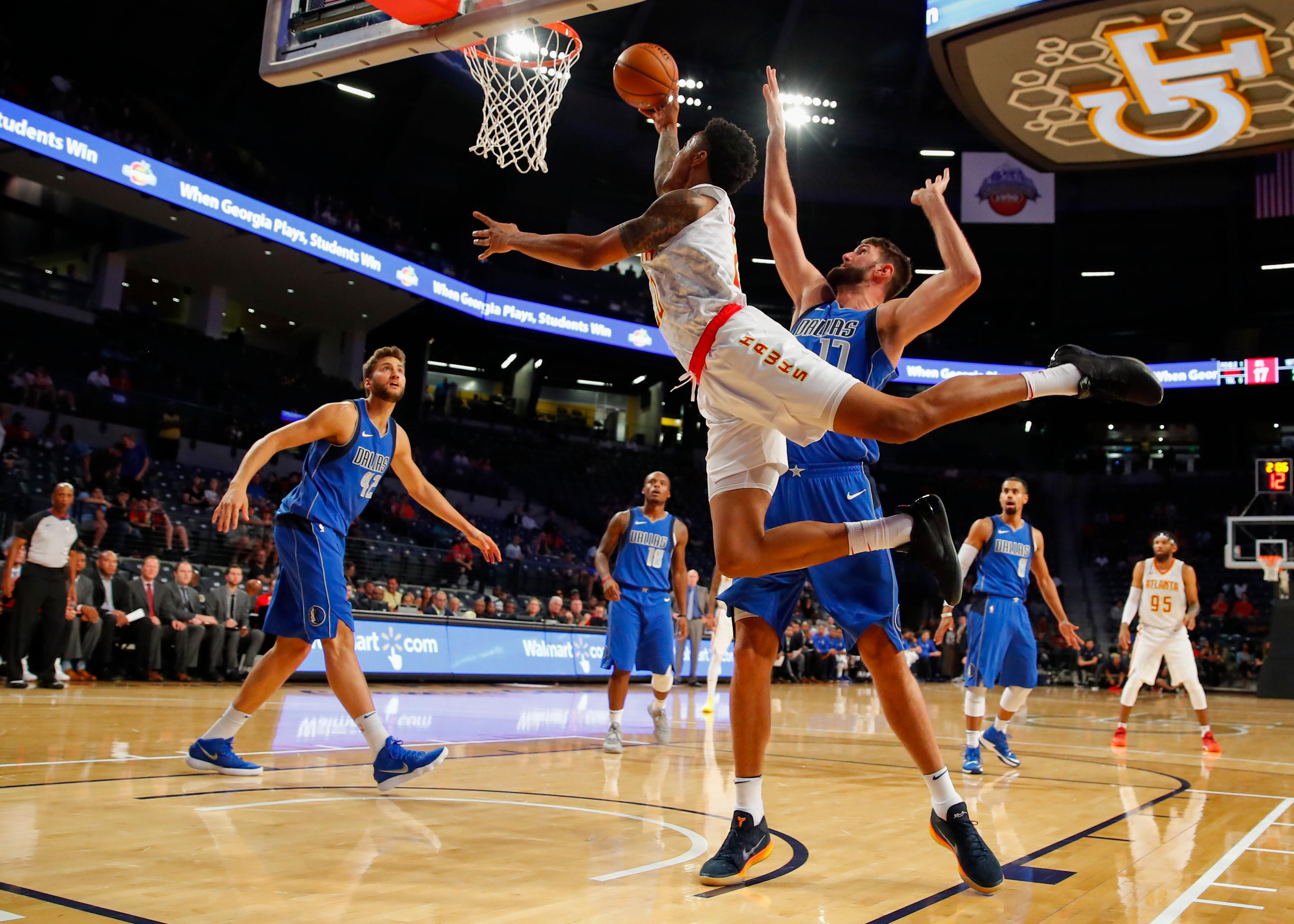 Atlanta Hawks forward John Collins (20) goes up to shoot as Dallas Mavericks center Jeff Withey (17) defends in the first half of an NBA preseason basketball game Thursday, Oct. 12, 2017, in Atlanta. (AP Photo/Todd Kirkland)