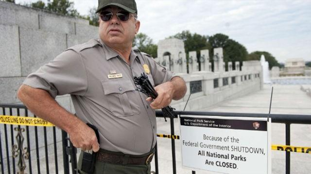 A U.S. park ranger places a closed sign on a barricade in front of the World War II Memorial in Washington on October 1.