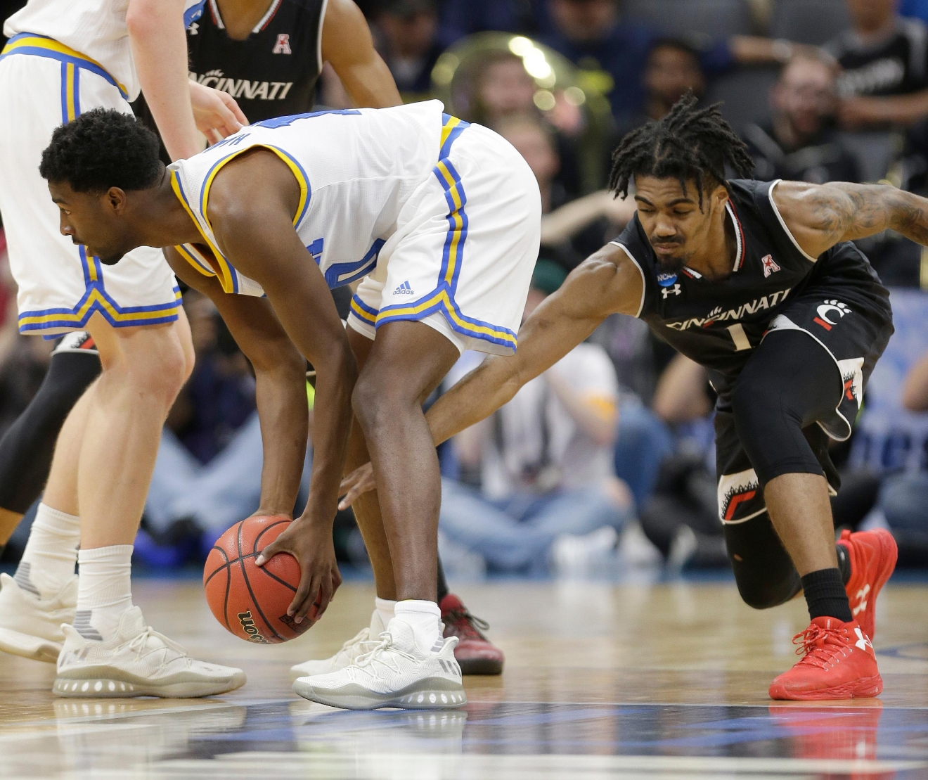 Cincinnati's Jacob Evans tries to steal the ball from UCLA guard Isaac Hamilton during the first half of a second-round game of the NCAA men's college basketball tournament in Sacramento, Calif., Sunday, March 19, 2017. (AP Photo/Rich Pedroncelli)