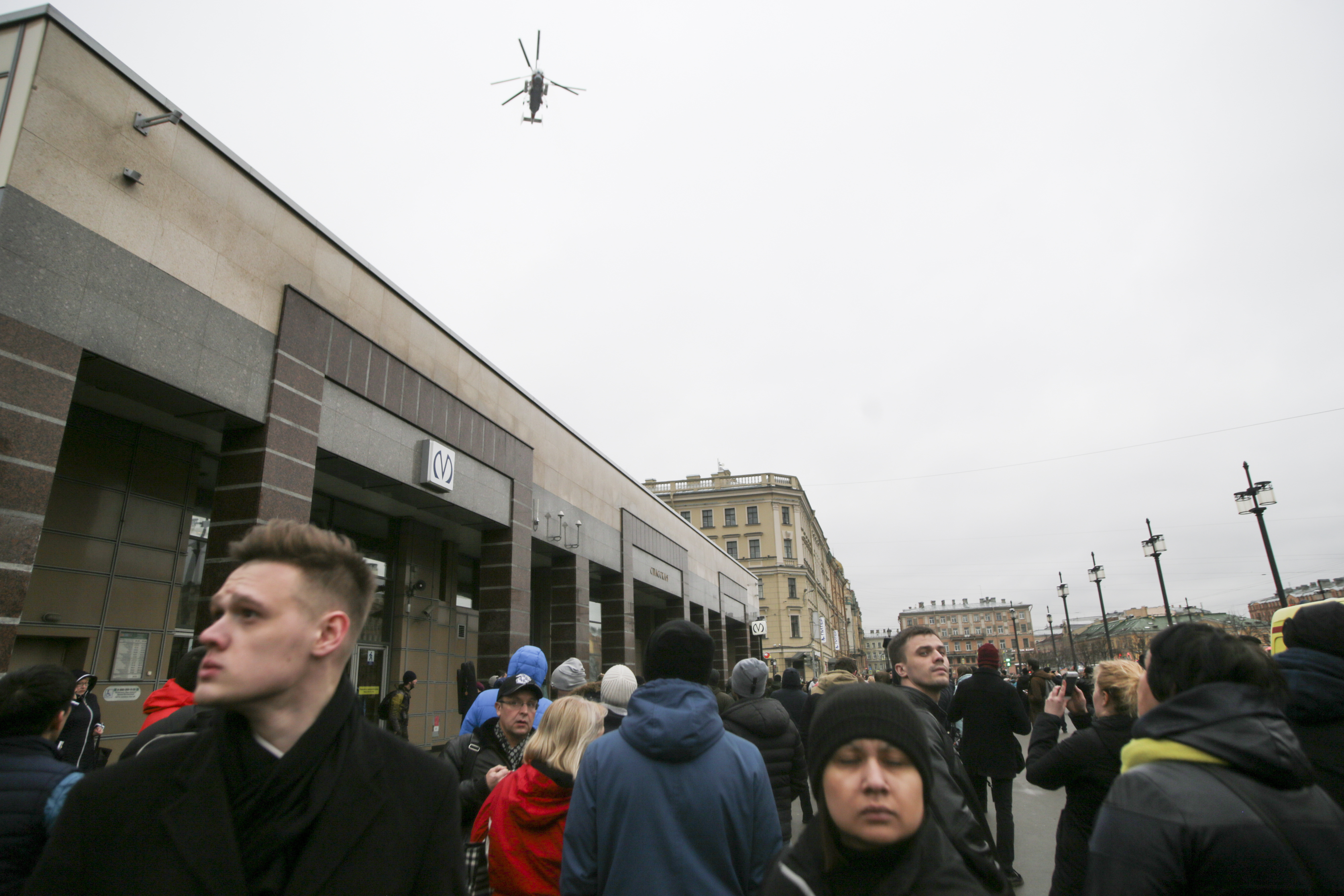 People walk past the entrance of Spasskaya subway station after a explosion in St.Petersburg's subway, Russia, Monday, April 3, 2017. The subway in the Russian city of St. Petersburg is reporting that there are fatalities and several people have been injured in an explosion on a subway train. (AP Photo/Evgenii Kurskov)