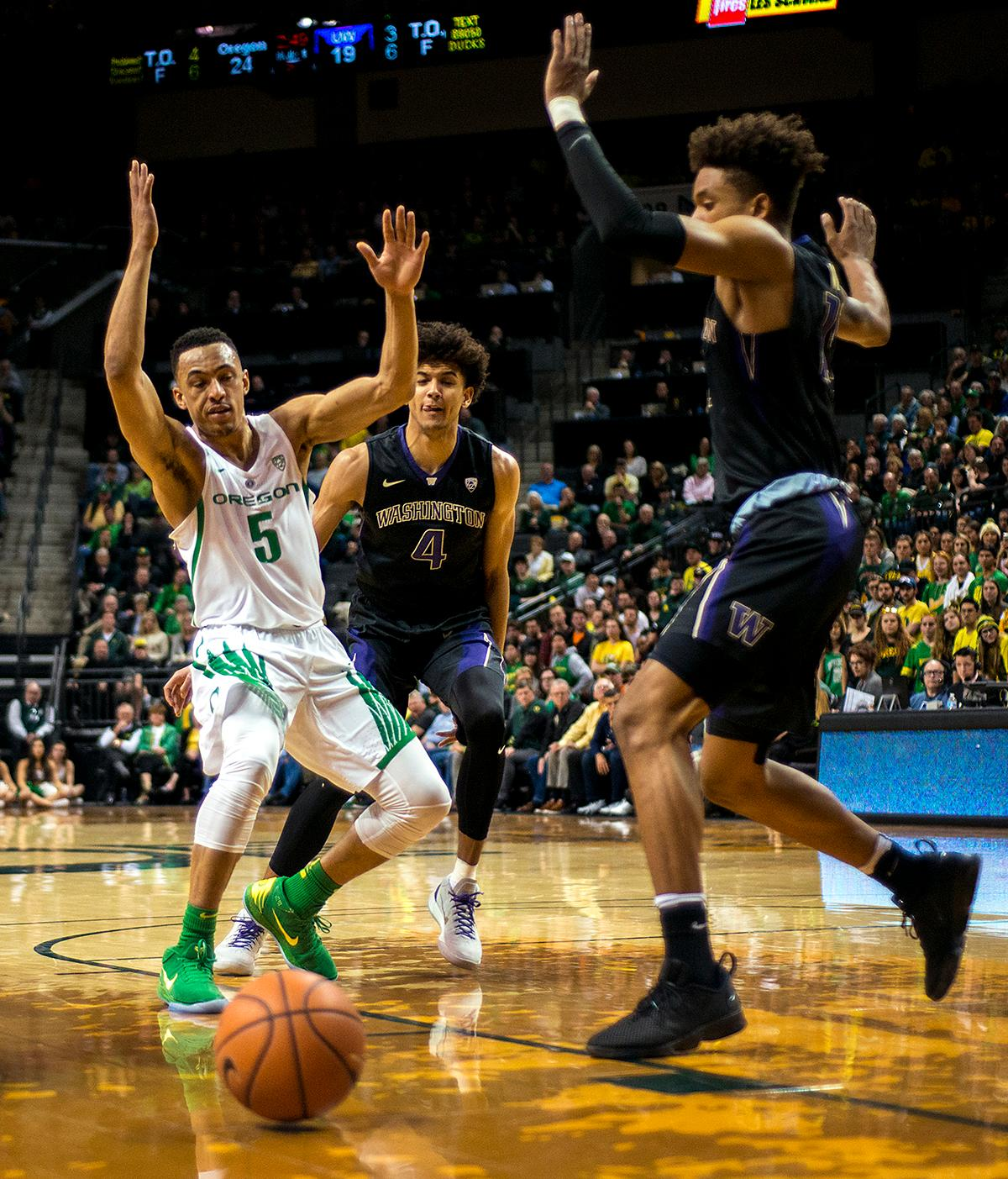 Oregon Ducks guard Elijah Brown (#5) and Washington Huskies guard Matisse Thybulle (#4) react as the ball become loose and rolls out of bounds. The Oregon Ducks defeated the Washington Huskies 65-40 on Thursday night at Matthew Knight Arena. Troy Brown, Junior led Oregon with 21 points to match his career high, and Kenny Wooten set a career best of seven shots blocked. The Ducks now stand 6-5 in the Pac-12 conference play. Photo by Abigail Winn, Oregon News Lab