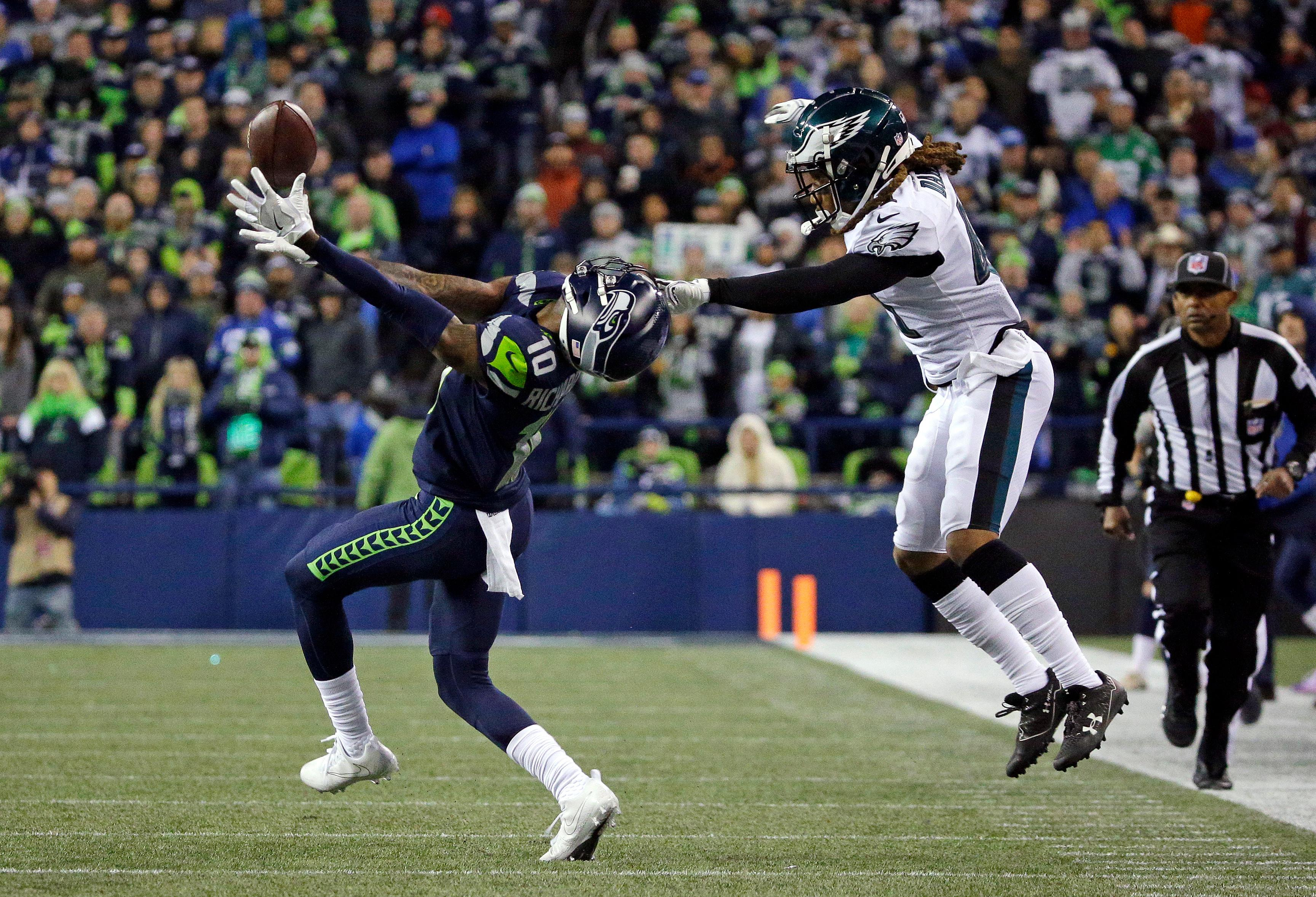 Seattle Seahawks' Paul Richardson, left, has his helmet pulled back as Philadelphia Eagles' Ronald Darby makes contact on a pass attempt to Richardson during the second half of an NFL football game, Sunday, Dec. 3, 2017, in Seattle. (AP Photo/Ted S. Warren)