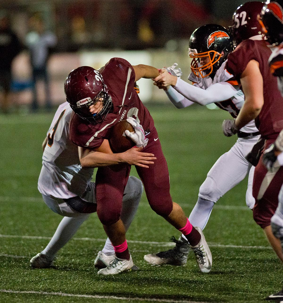 Roseburg Indians defensive back Colin Rietmann (#27) attempts to slow the forward motion of Willamette Wolverines running back Tanner Webb (#20). Roseburg defeated Willamette 21-20 at Wolverine Stadium. Photo by Dan Morrison, Oregon News Lab