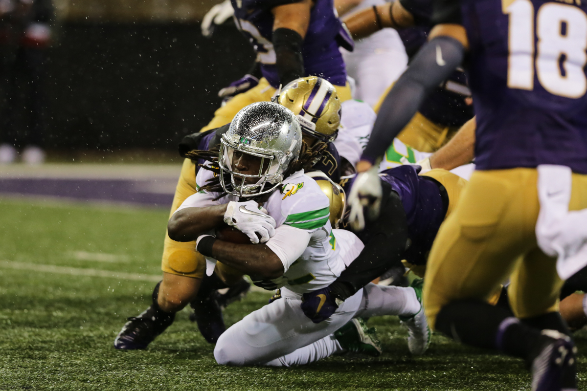 Oregon running back Darrian Felix (#22) is dragged down from behind by two Washington defenders. The Oregon Ducks fell to the Washington Huskies 38 - 3 on a cold and rainy night in Seattle, Washington.  Oregon opened the game with a field goal on their first drive and was held scoreless from then on.  Photo by Austin Hicks, Oregon News Lab
