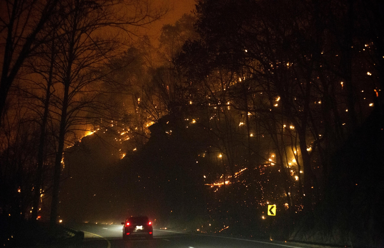 Fire erupts on both side of Highway 441 between Gatlinburg and Pigeon Forge, Tenn., Monday, Nov. 28, 2016. In Gatlinburg, smoke and fire caused the mandatory evacuation of downtown and surrounding areas, according to the Tennessee Emergency Management Agency. (Jessica Tezak/Knoxville News Sentinel via AP)