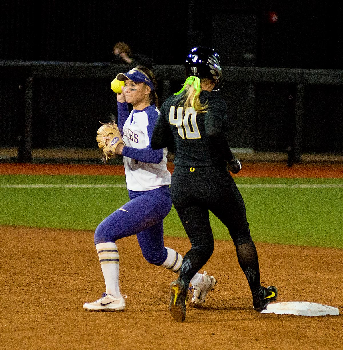 Ducks Miranda Elish (#40) is out at second and Huskies shortstop Ali Aguilar (#1) attempts to turn a double play. In Game Two of a three-game series, the University of Oregon Ducks softball team defeated the University of Washington Huskies 4-1 Friday night in Jane Sanders Stadium. Danica Mercado (#2), Alexis Mack (#10) and Mia Camuso (#7) all scored in the win, Mack twice. The Ducks play the Huskies for the tie breaker on Saturday with the first pitch at noon. Photo by Dan Morrison, Oregon News Lab