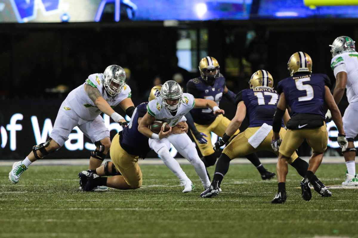 Oregon quarterback Braxton Burmeister (#11) is tackled by a Washington defender. The Oregon Ducks are trailing the Washington Huskies 3 - 17 at halftime.  The Huskies rallied with a 17-point second quarter after a slow first quarter on a cold and rainy night in Seattle, Washington.  Photo by Austin Hicks, Oregon News Lab