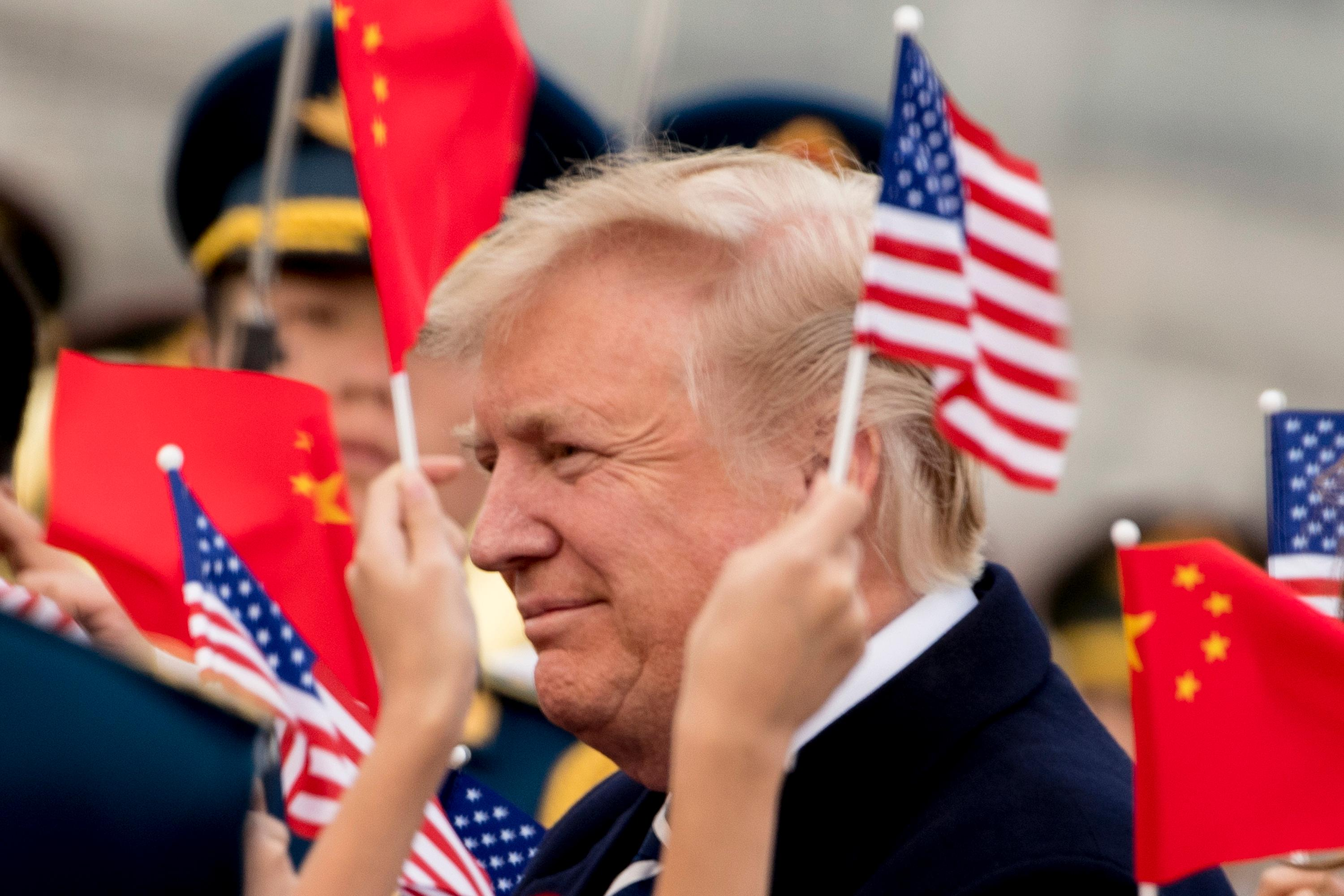 Children wave U.S. and Chinese flags as President Donald Trump arrives at Beijing Airport, Wednesday, Nov. 8, 2017, in Beijing, China.(AP Photo/Andrew Harnik)<p></p>