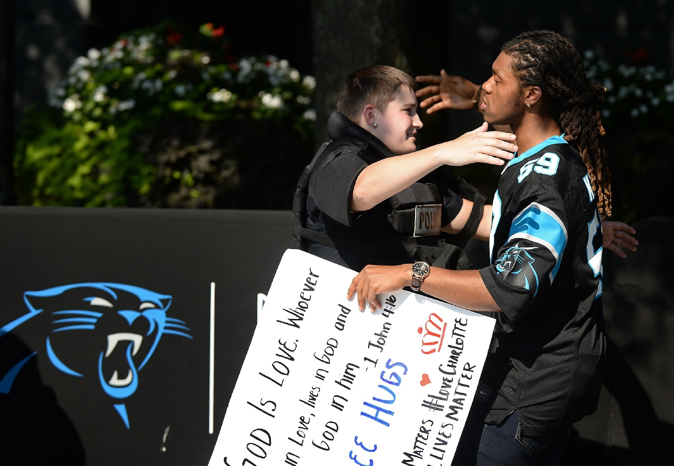 JaGerran Knight, right, reaches out to hug a Charlotte-Mecklenburg police officer at Bank of America Stadium, where people were protesting, in Charlotte, N.C., Sunday, Sept. 25, 2016. The Carolina Panthers hosted an NFL football game with the Minnesota Vikings at the stadium. When the national anthem was played, the protesters all dropped to one knee as many NFL players have been doing for weeks to call attention to issues, including police shootings. (Diedra Laird/The Charlotte Observer via AP)