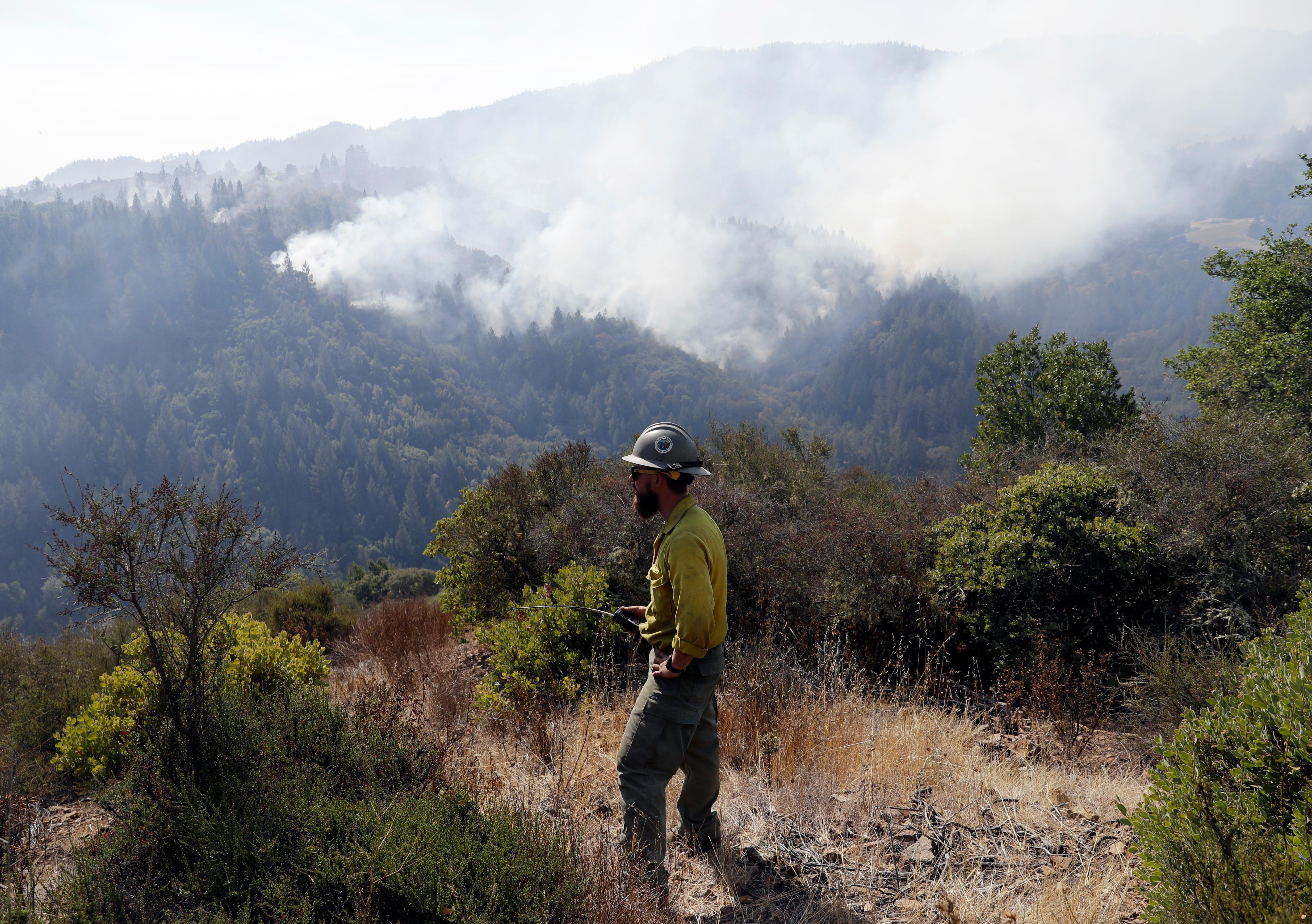 Jeff Wolf, with the El Dorado Hot Shots, out of Pollock Pines, Calif., monitors a wildfire from a mountain top, Sunday, Oct. 15, 2017, in Oakville, Calif. With the winds dying down, fire officials in California say they are finally getting the upper hand against the wildfires that have devastated wine country and other parts of the state over the past week. (AP Photo/Marcio Jose Sanchez)